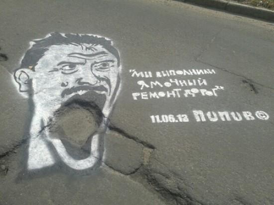 На автодорожных ямах Киева написали портрет Попова